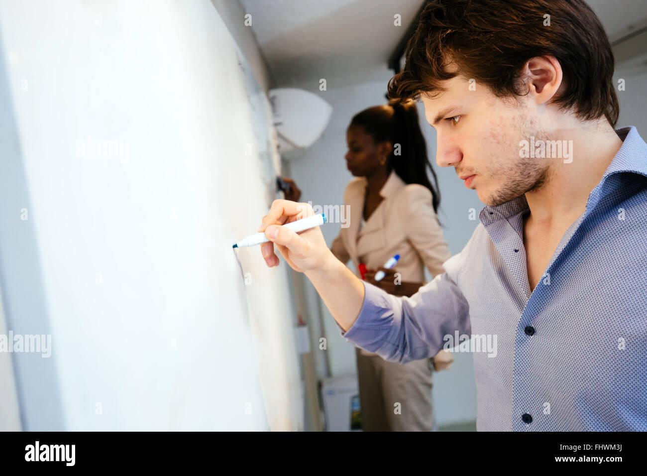 Des gens intelligents écrit sur le tableau blanc à la recherche d'une solution Photo Stock