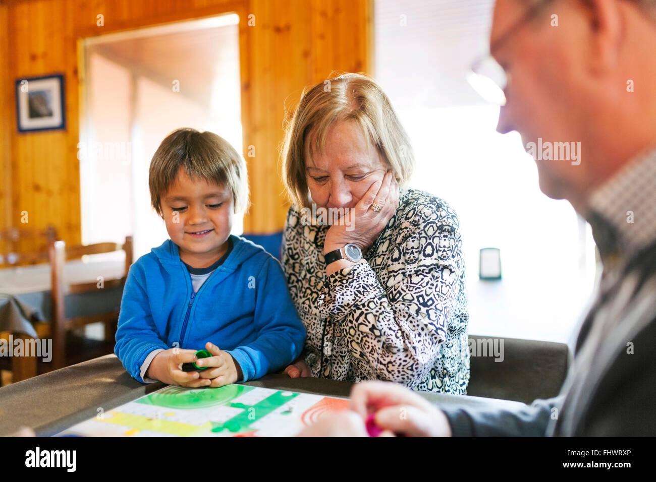 Les grands-parents jouer ludo leur petit-fils Photo Stock