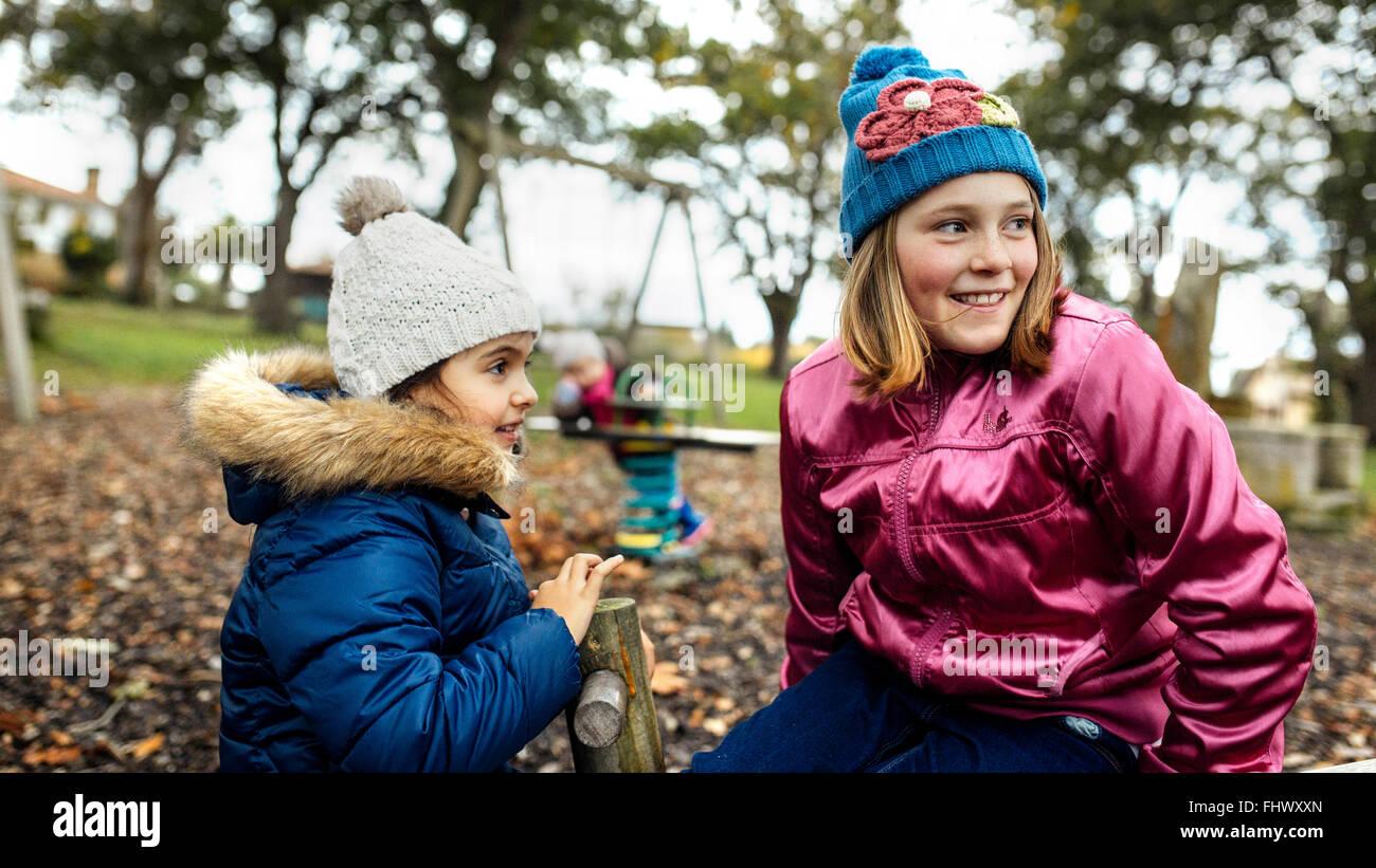 Deux jeunes filles de regarder quelque chose sur une aire à l'automne Photo Stock