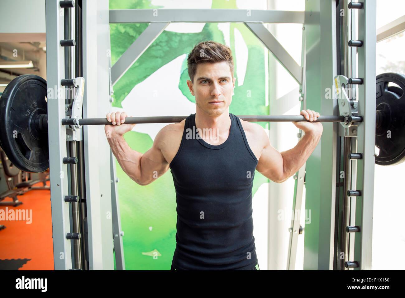Bel homme de la formation en salle de sport pour rester en forme et solide Photo Stock