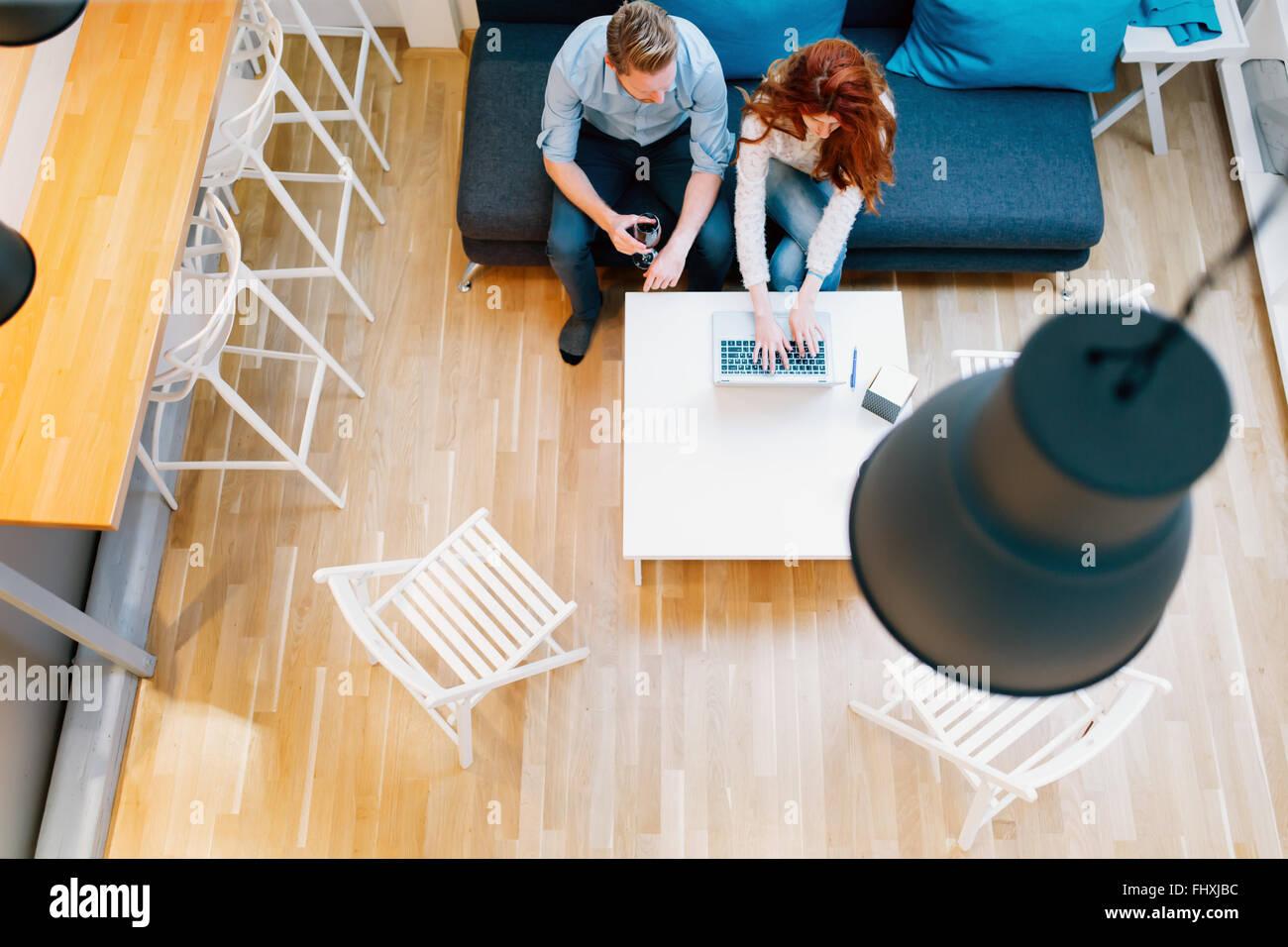 Couple browsing web dans son ensemble dans la salle de séjour vue d'en haut Photo Stock
