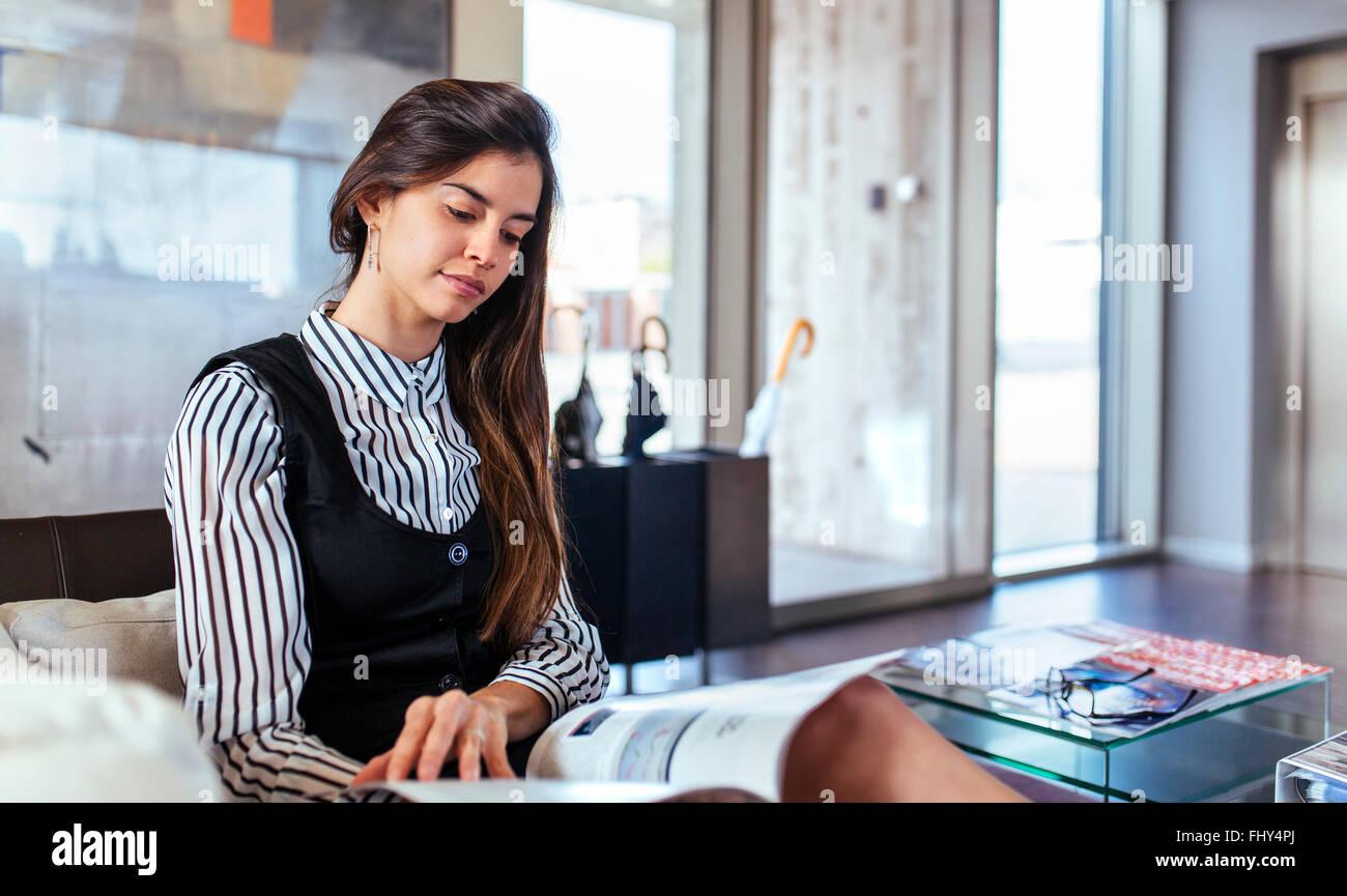 Young woman reading magazine à l'aire d'attente d'un bureau Photo Stock