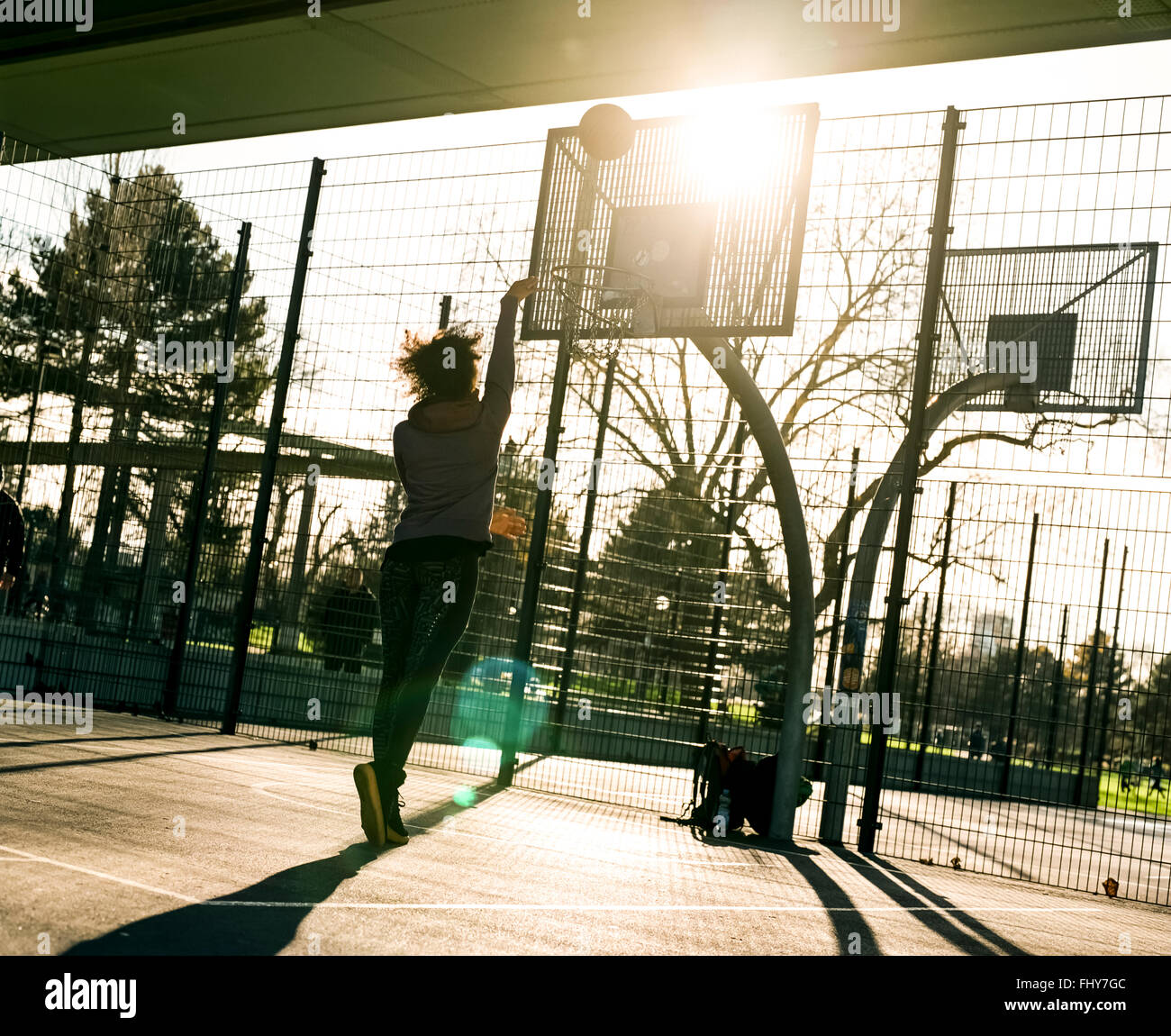 Vue arrière de jeune femme jetant sur un terrain de basket-ball Photo Stock