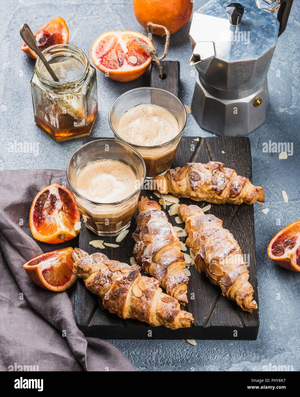 Style Italien accueil petit déjeuner. Café Latte croissants aux amandes et oranges sur sanglant rouge Photo Stock