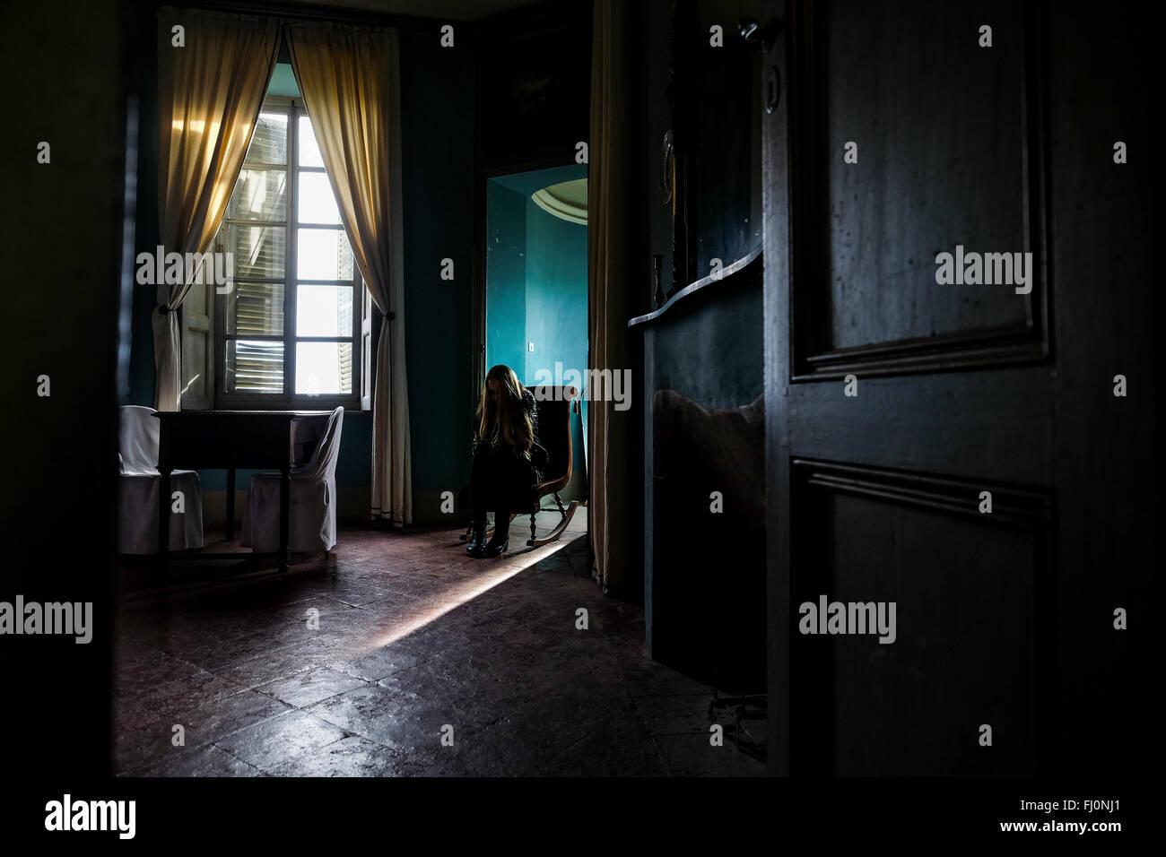 jeune femme assise dans une chambre sombre banque d'images, photo