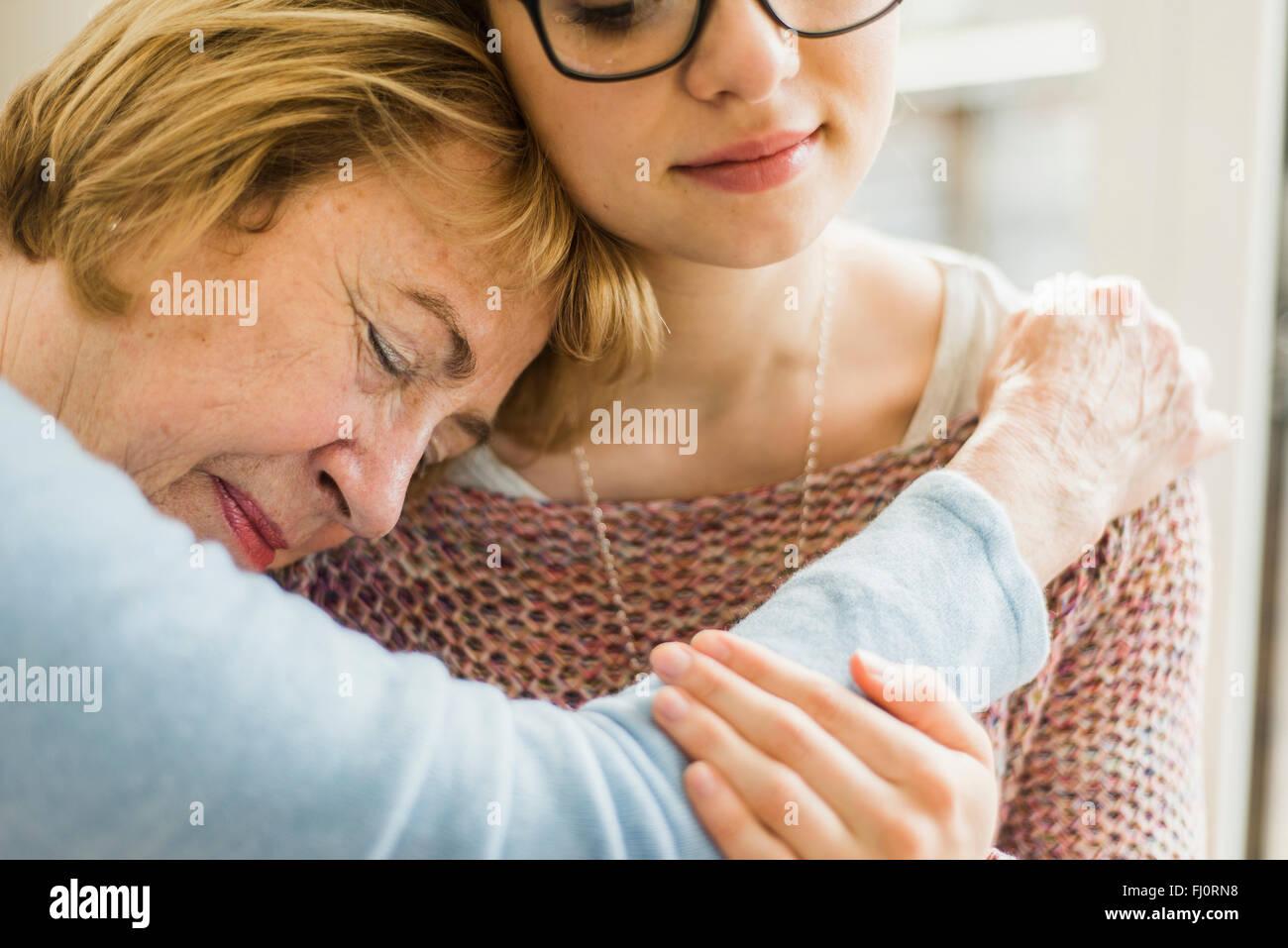 Senior woman with closed eyes appuyé contre l'épaule de la jeune femme Photo Stock