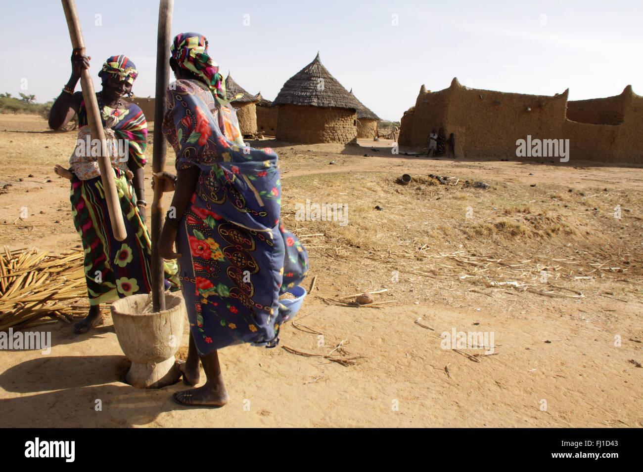 Battre les femmes peules traditionnelles millet dans village près de Gorom Gorom, région du Sahel, Burkina Photo Stock