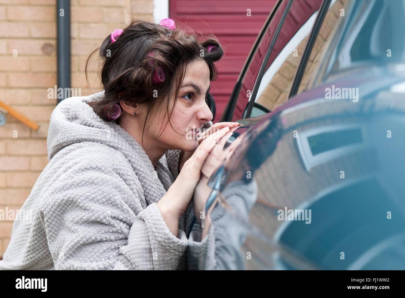 Femme en robe de chambre et les bigoudis en regardant par la fenêtre d'une voiture Photo Stock