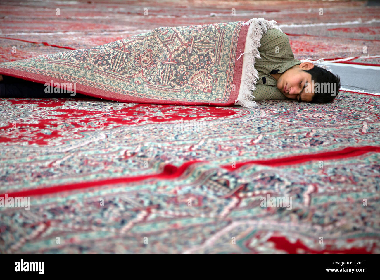 Man sleeping enveloppé dans un tapis en Iran dans le mausolée de l'Ayatollah Khomeini, Téhéran, Photo Stock