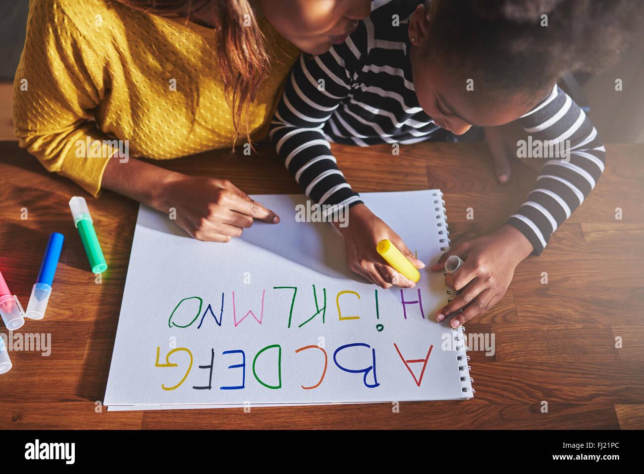 Vue de dessus de petite fille l'apprentissage de l'alphabet à l'aide de crayons de couleur Photo Stock
