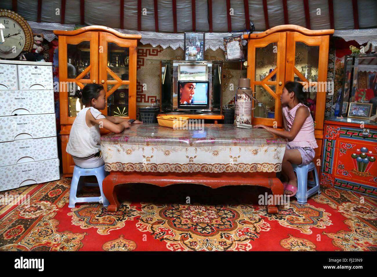 Deux jeunes filles regardent la télévision dans un foyer traditionnel appelé ger ou yourte en Mongolie Photo Stock