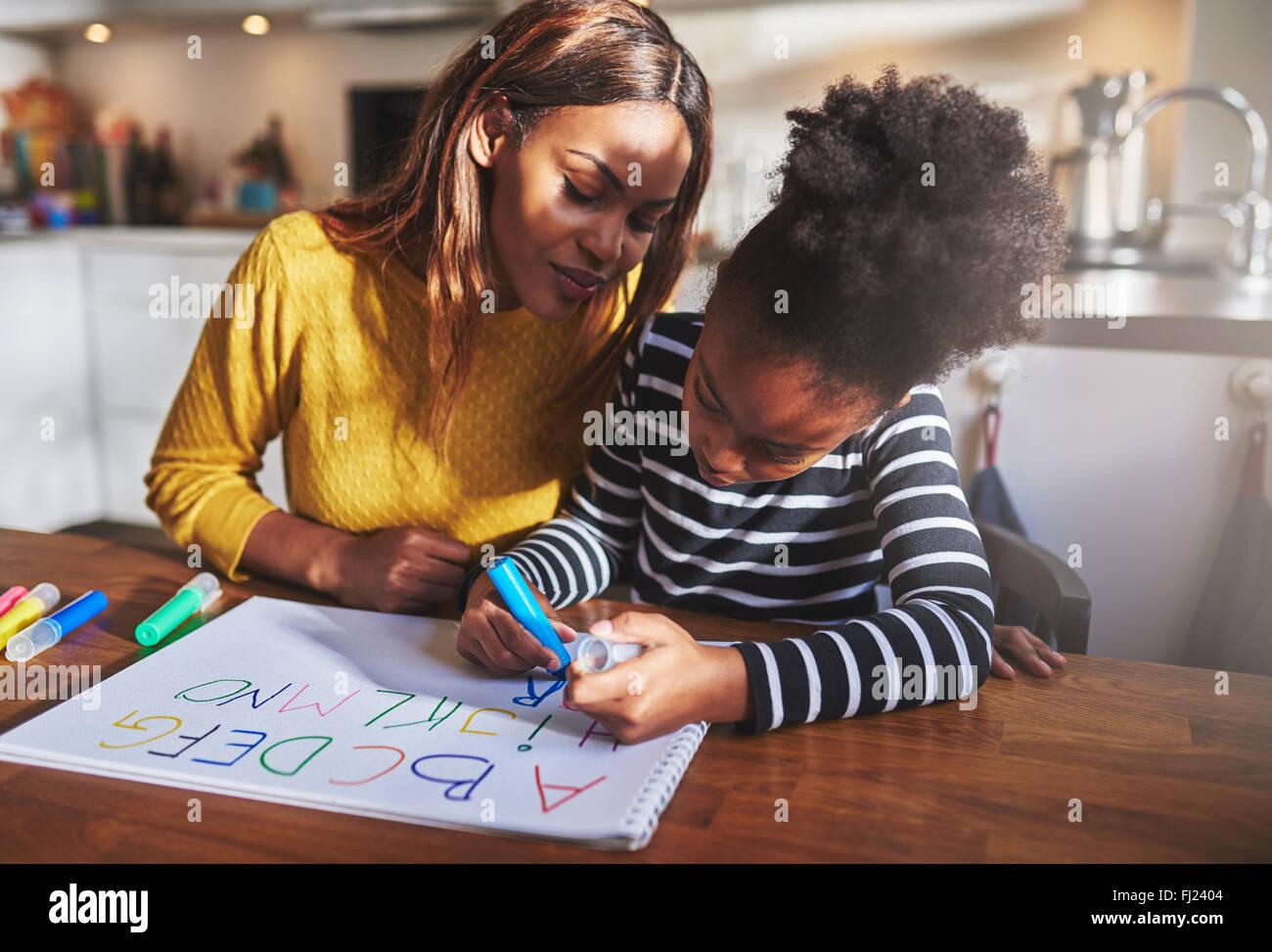 Petite fille l'apprentissage de l'alphabet à l'aide de lettres de couleur Banque D'Images