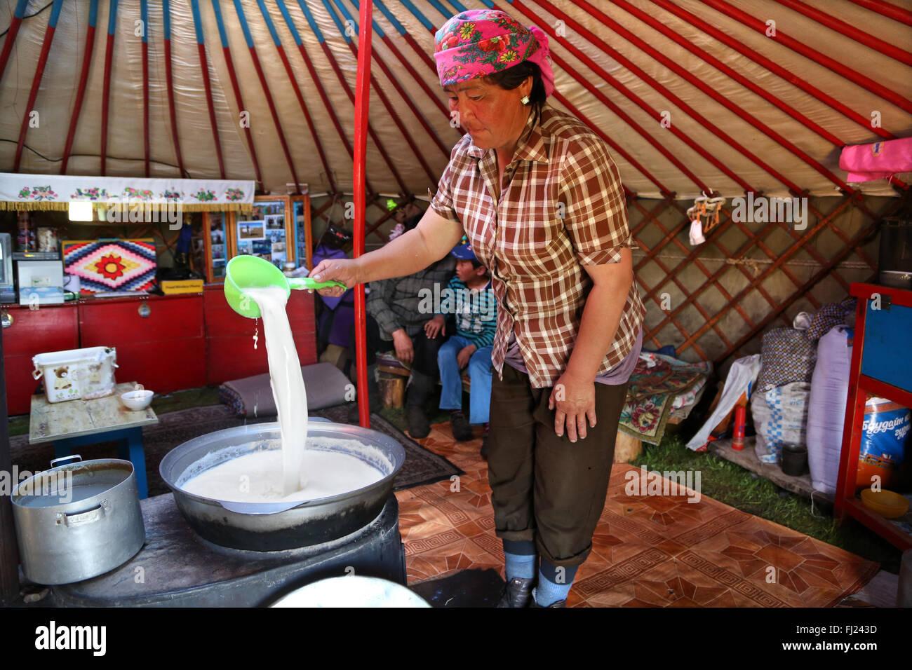 Une femme nomade est bouillante et la préparation traditionnelle kumis l de lait dans une yourte traditionnelle Banque D'Images