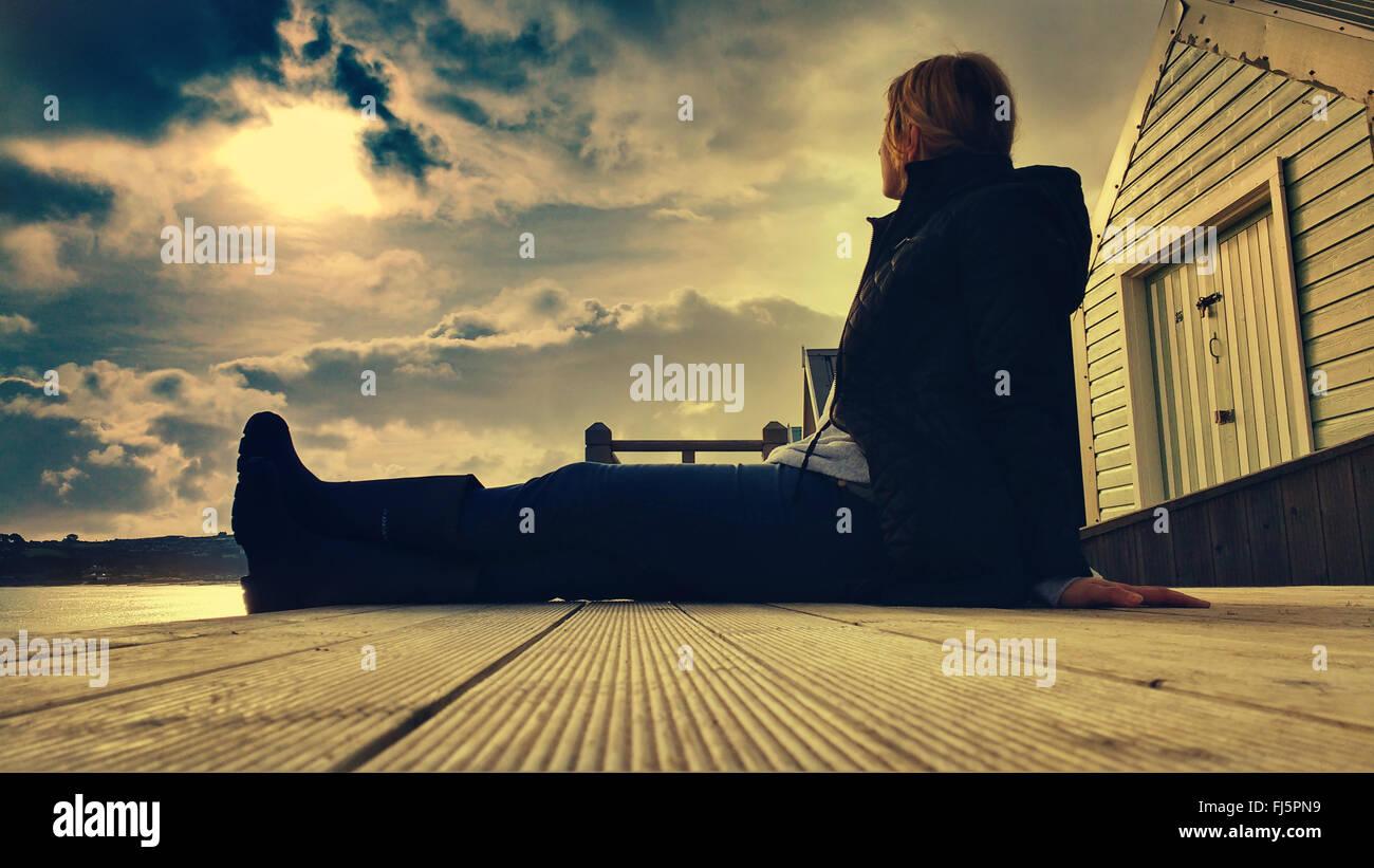 Jeune femme assise confortablement sur plancher cabine de plage en bois Photo Stock