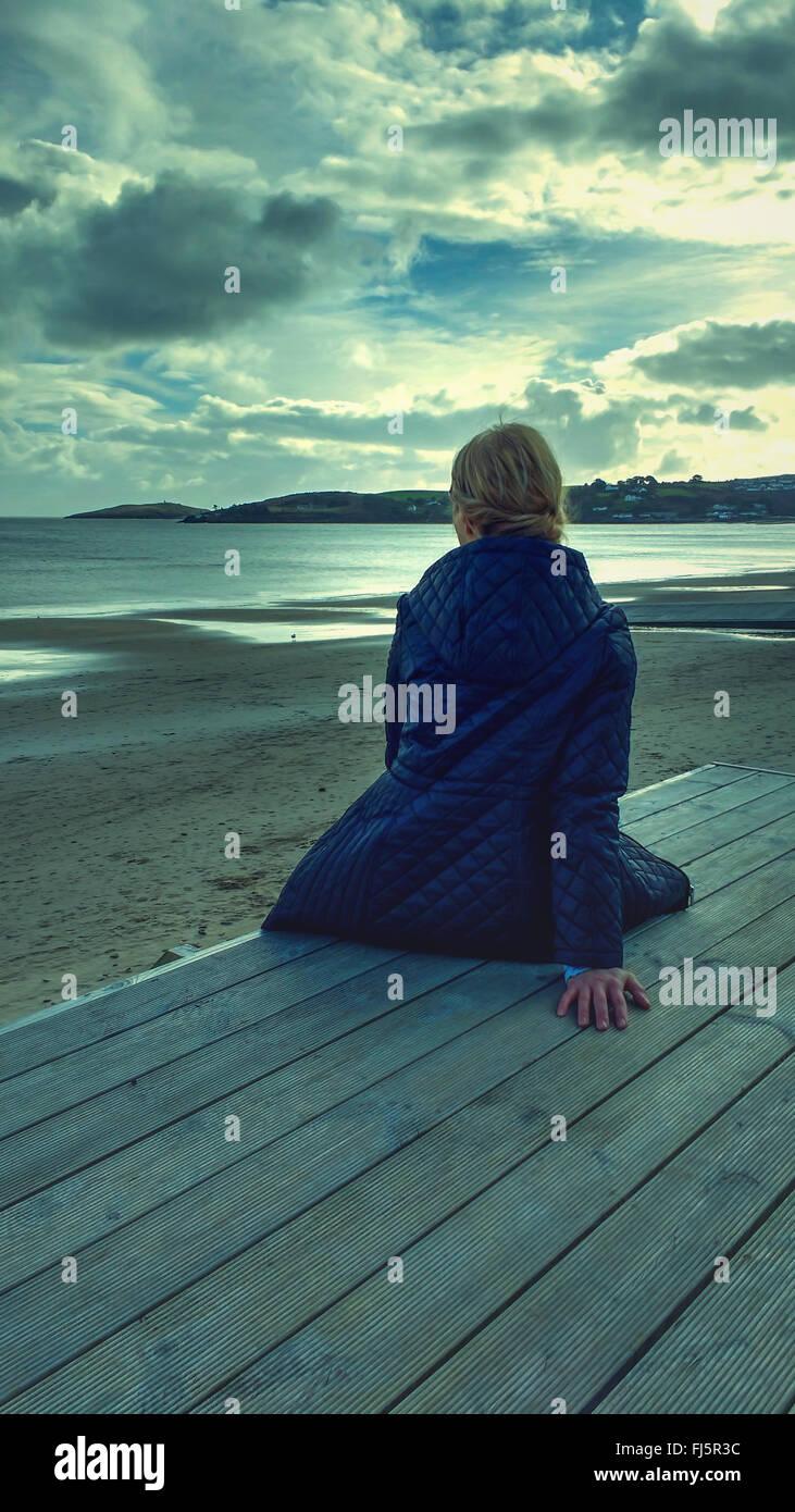 Jeune femme assise sur le bois on beach Banque D'Images