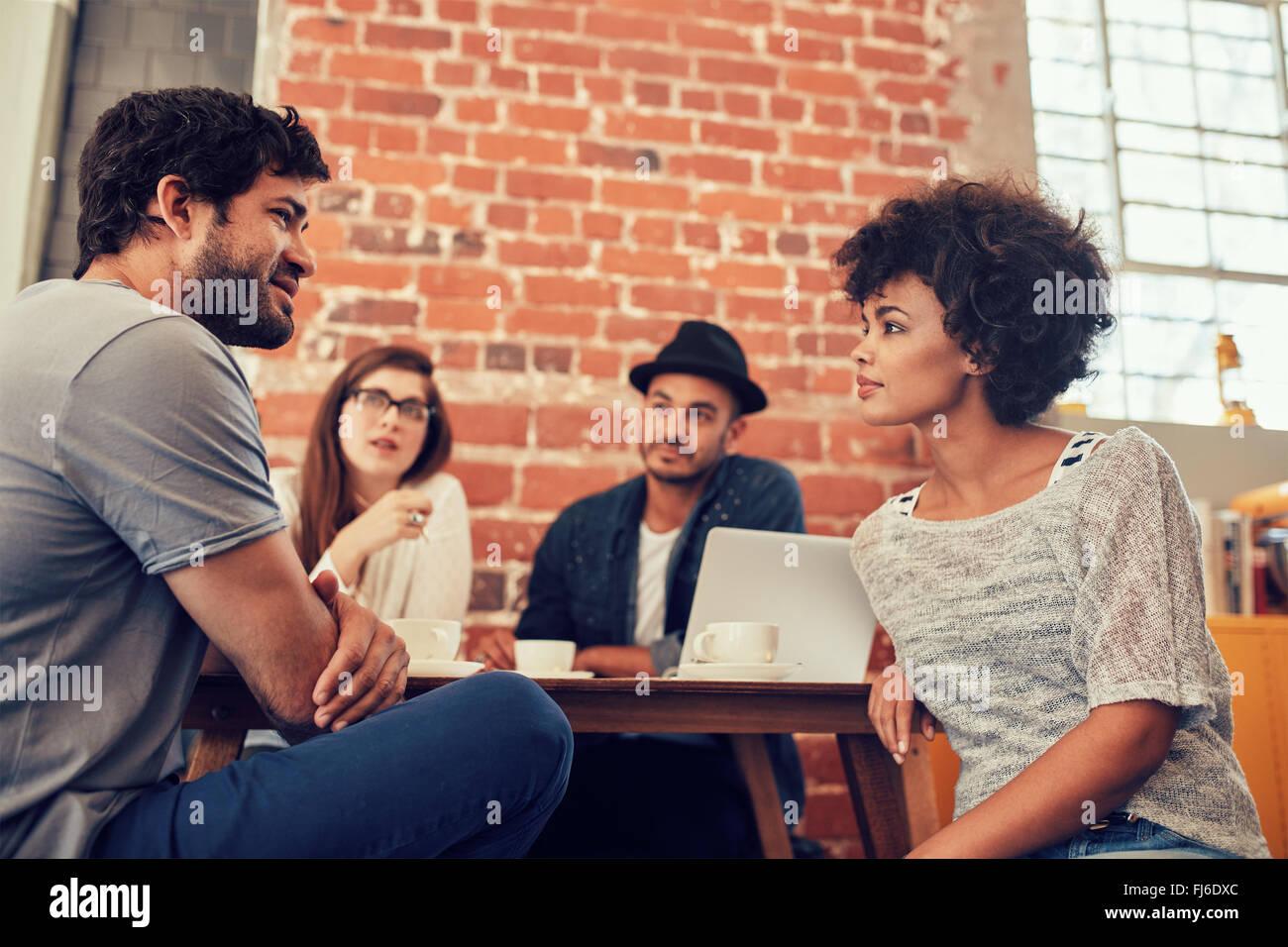 Portrait de jeunes amis assis à une table de café et de parler. Groupe de jeunes rencontre dans un café. Photo Stock