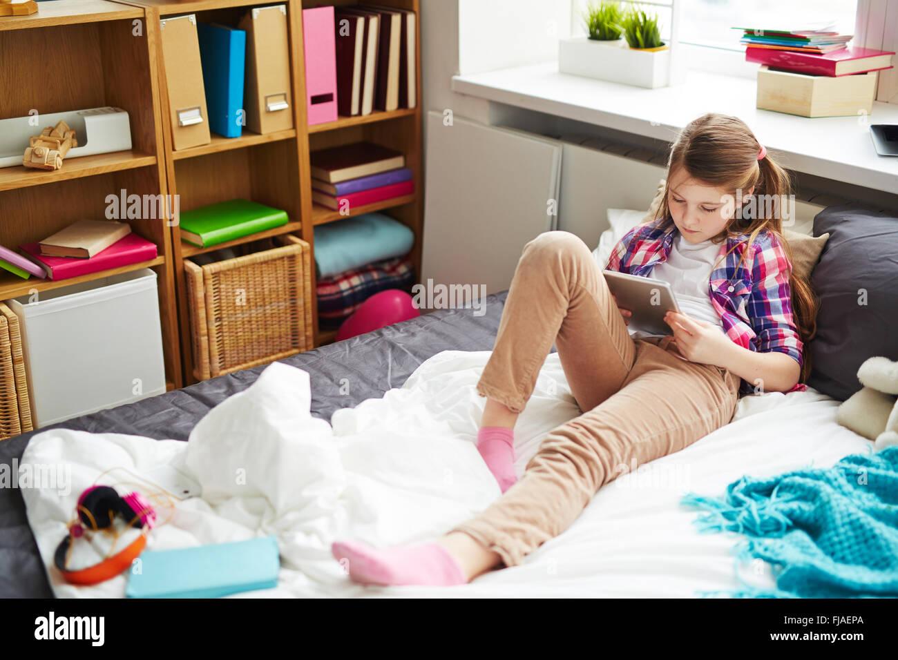 Pretty woman avec surface tactile networking à la maison Photo Stock