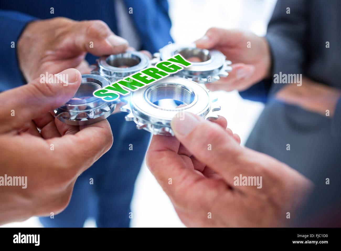 Synergie contre des collègues d'affaires holding cog Photo Stock