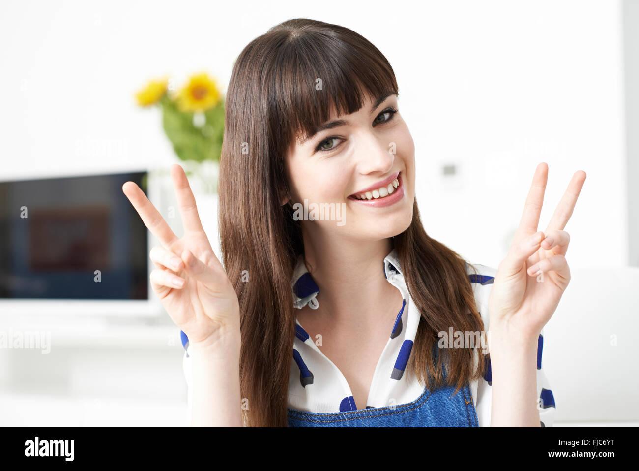 Jeune femme faisant la paix geste avec les mains Photo Stock