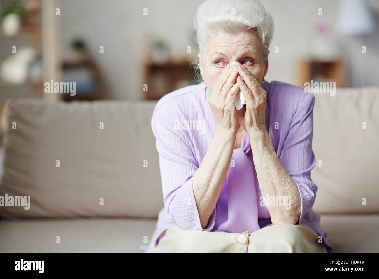 Sad senior woman sitting on sofa et pleurer Photo Stock