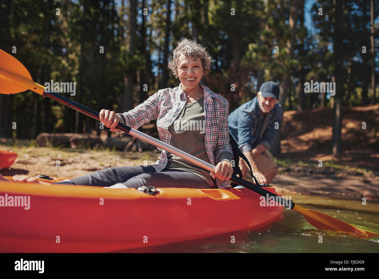 Portrait of senior woman in a kayak holding pagaies. Femme canoë avec l'homme en arrière-plan, au Photo Stock