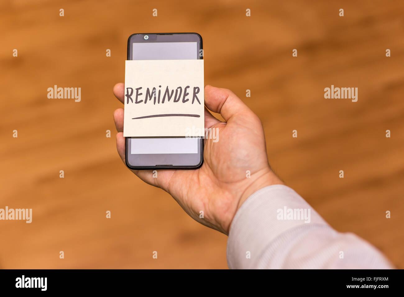 Human hand holding smartphone avec une note jaune collé sur elle. Rappel Le mot est écrit sur la note. Photo Stock