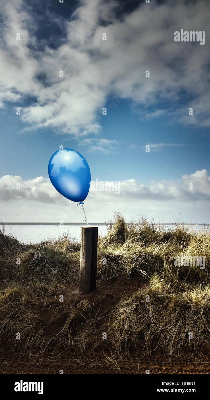 Paysage de plage avec un poteau en bois et un ballon bleu attaché à lui Photo Stock