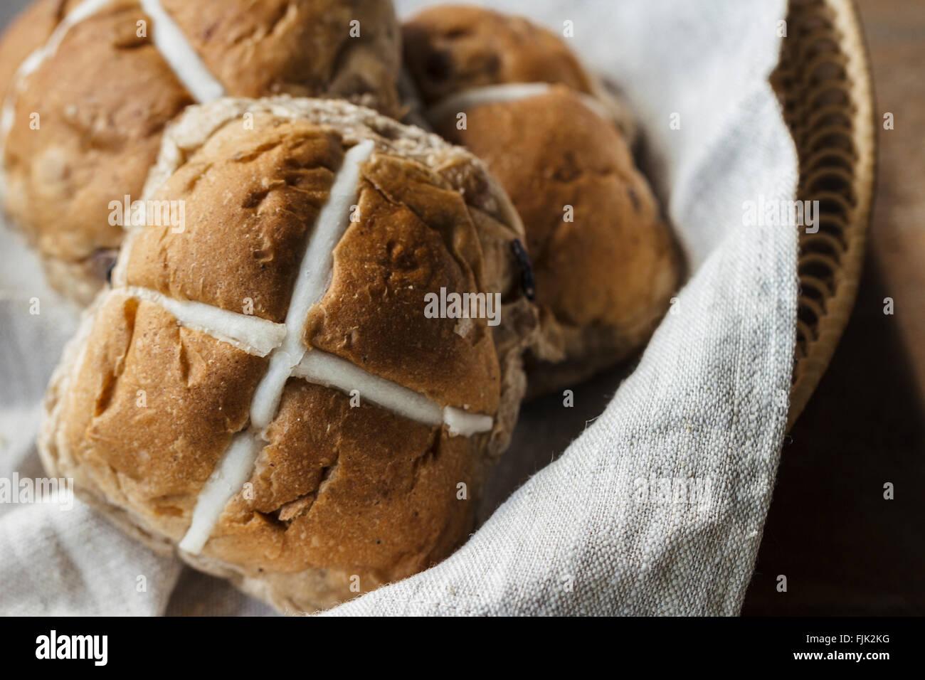Trois brioches de Pâques dans un panier sur une table en bois rustique Photo Stock