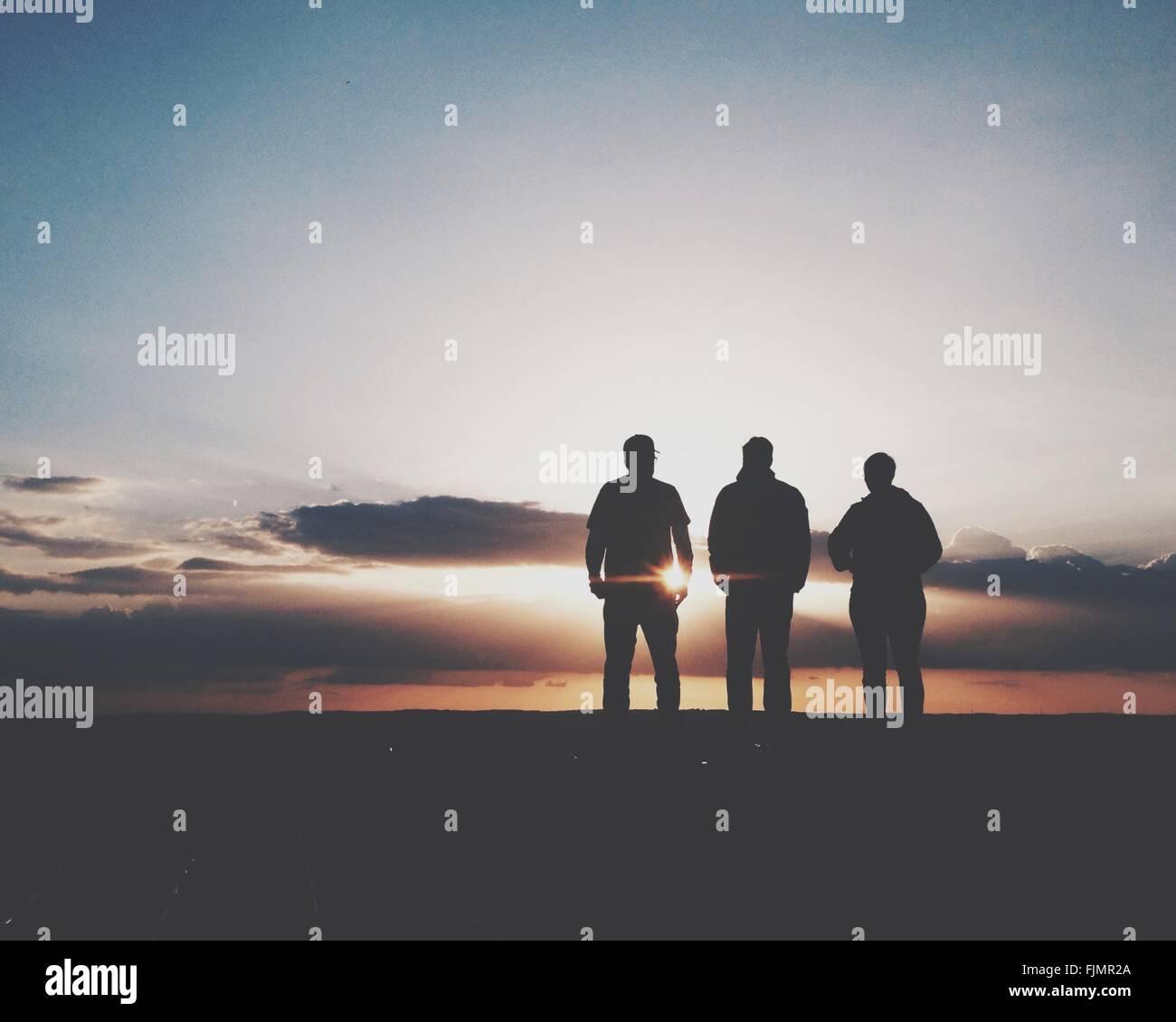 Silhouette de trois personnes debout au coucher du soleil Photo Stock