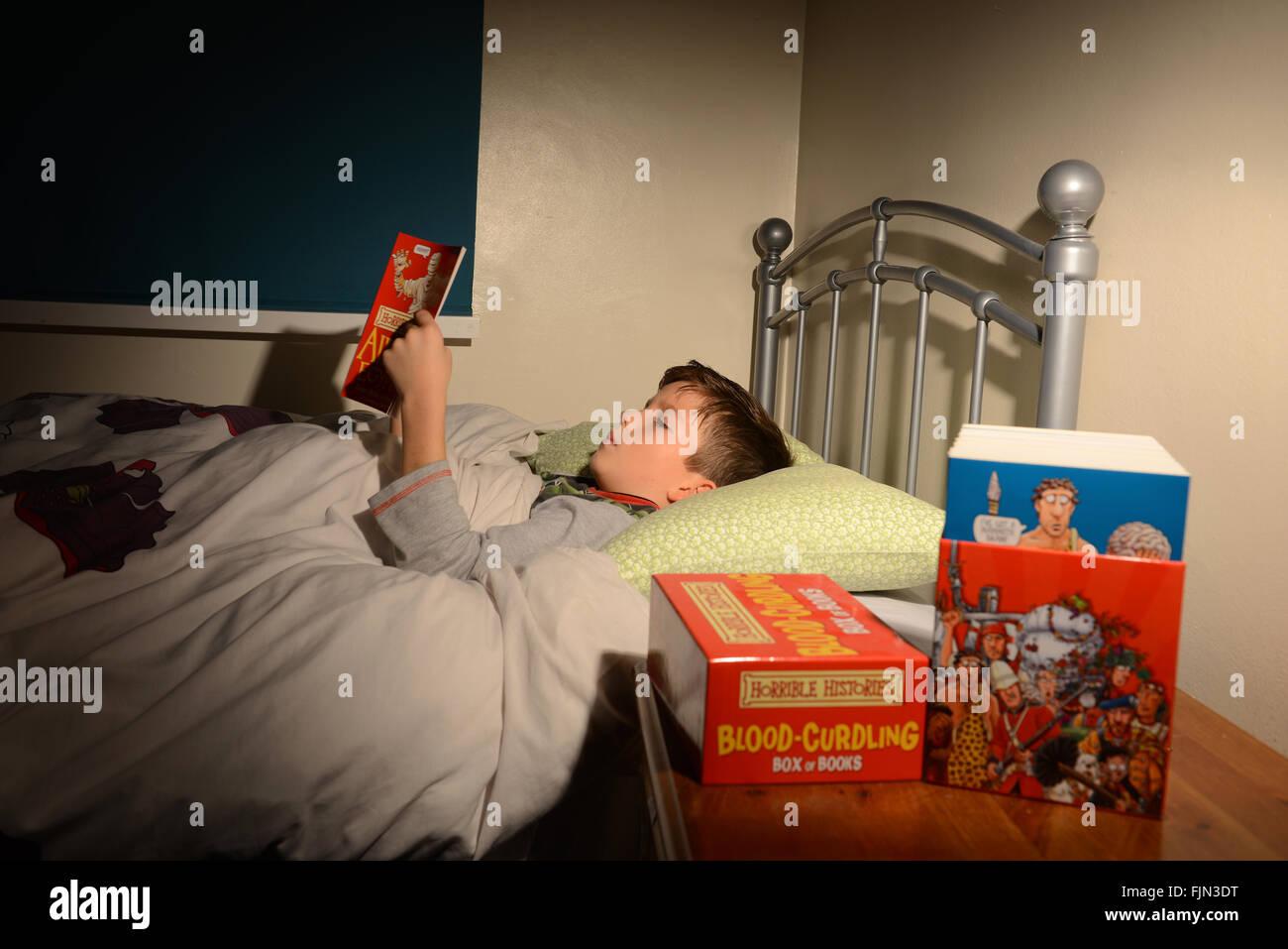 boy reading 39 histoires horribles 39 book in bed enfant lire un livre couch dans son lit l. Black Bedroom Furniture Sets. Home Design Ideas