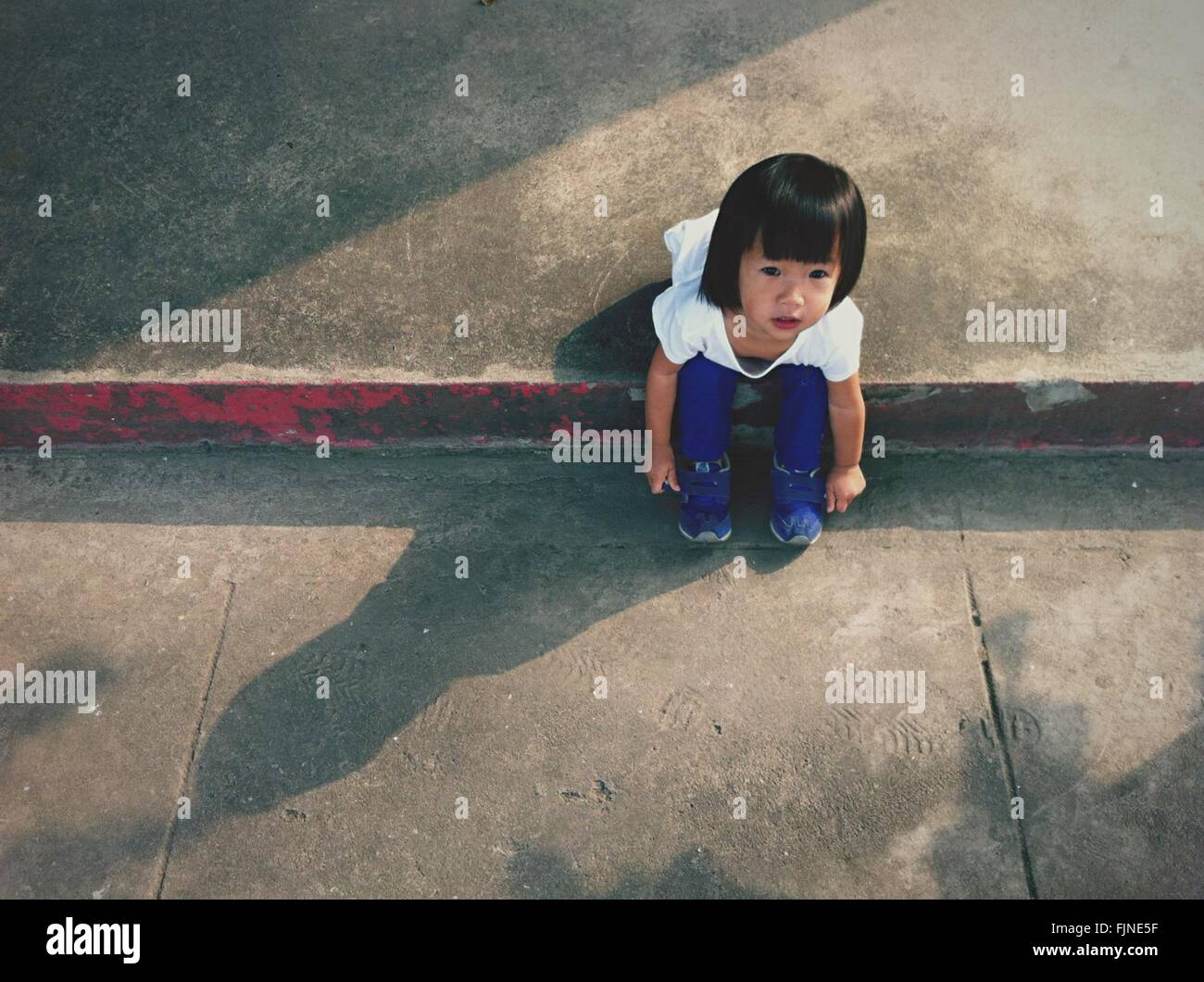 High Angle View of Girl Sitting on Sidewalk Banque D'Images