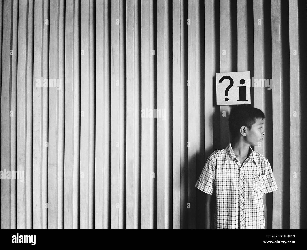Vue avant du garçon debout contre le mur Photo Stock