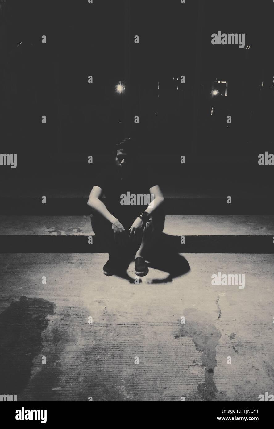 Homme seul assis sur sentier dans le noir Photo Stock