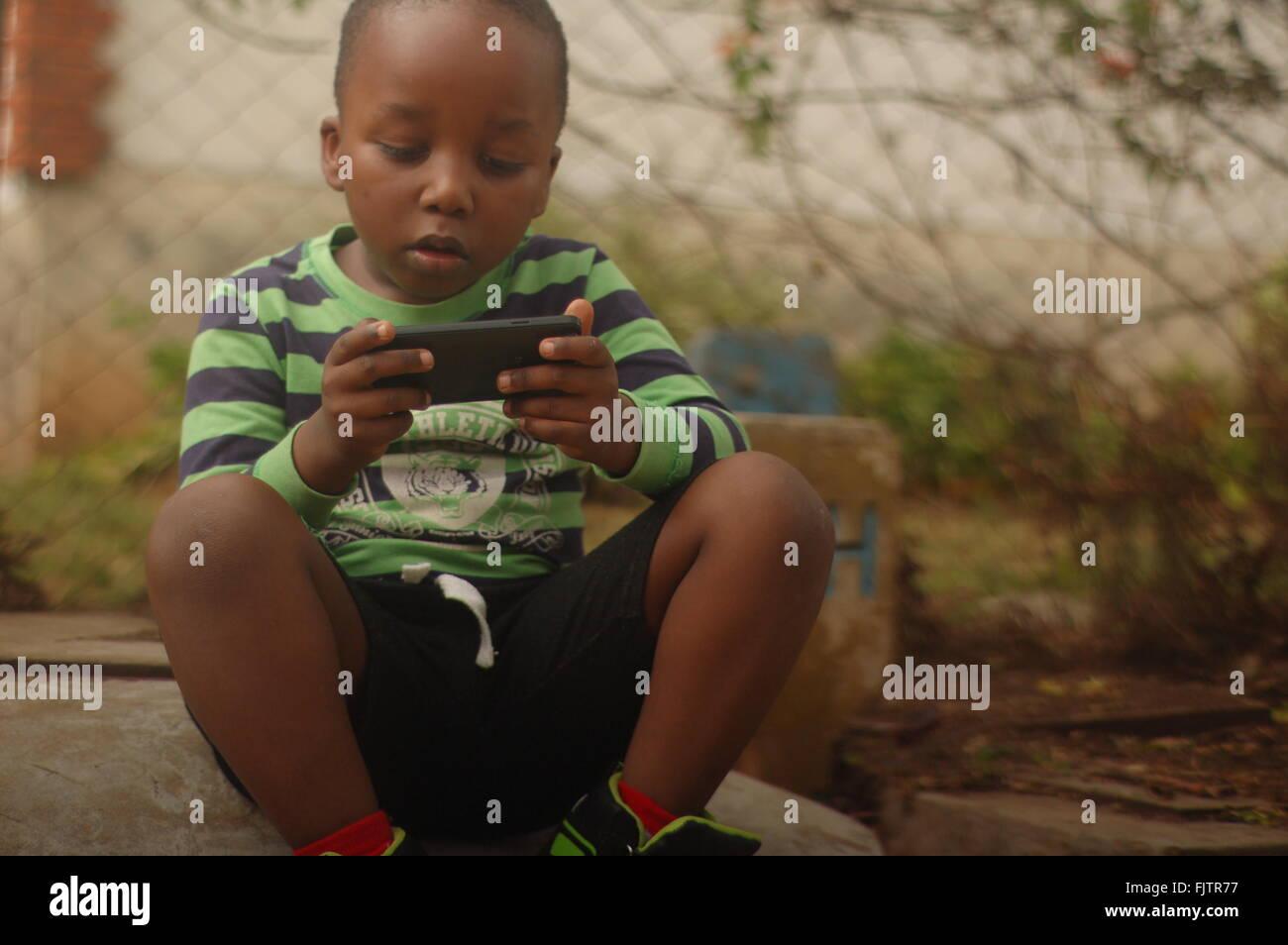 Curieux Garçon jouant avec Smart Phone at Field Photo Stock