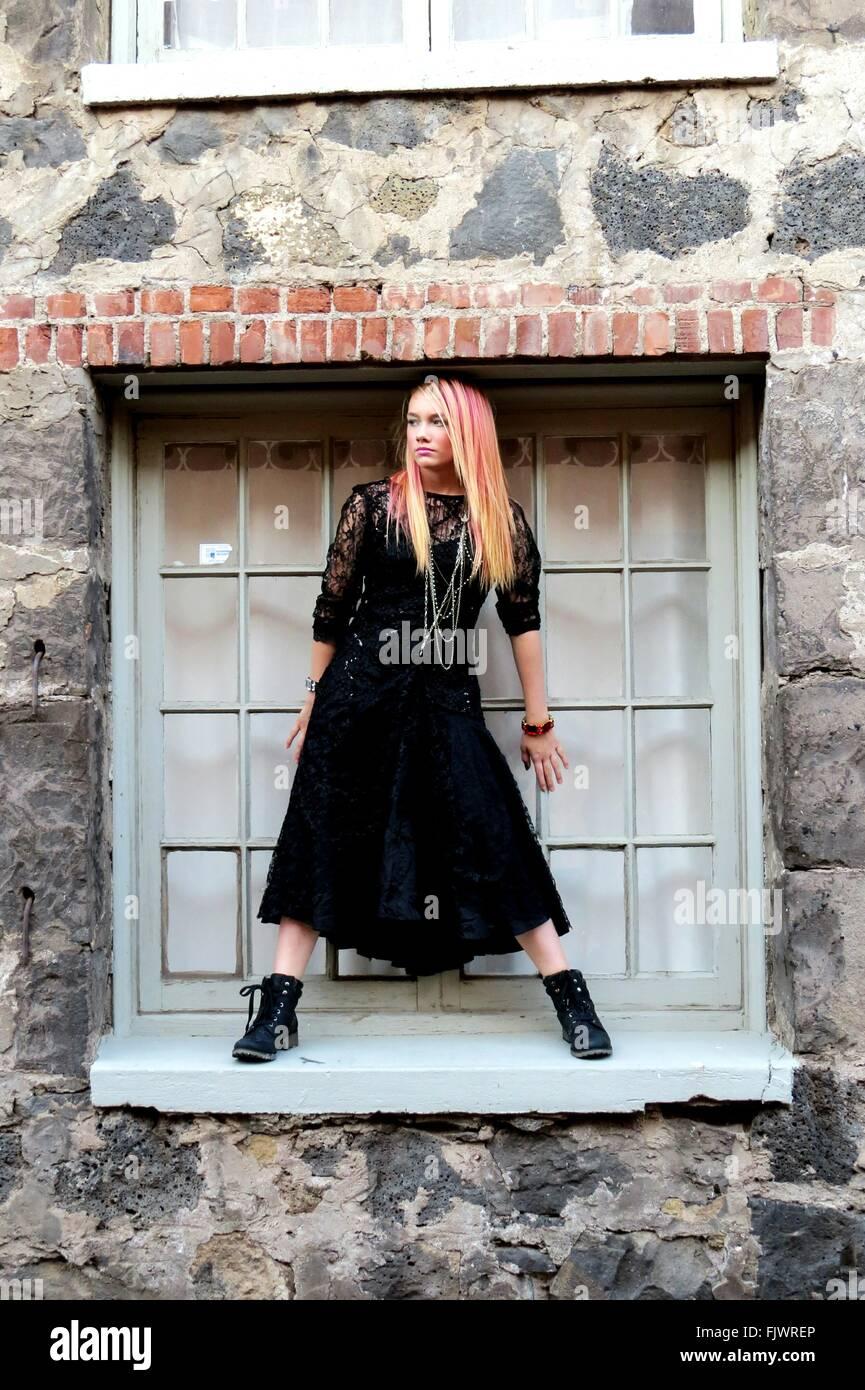 Jeune femme avec des jambes debout sur la fenêtre Photo Stock
