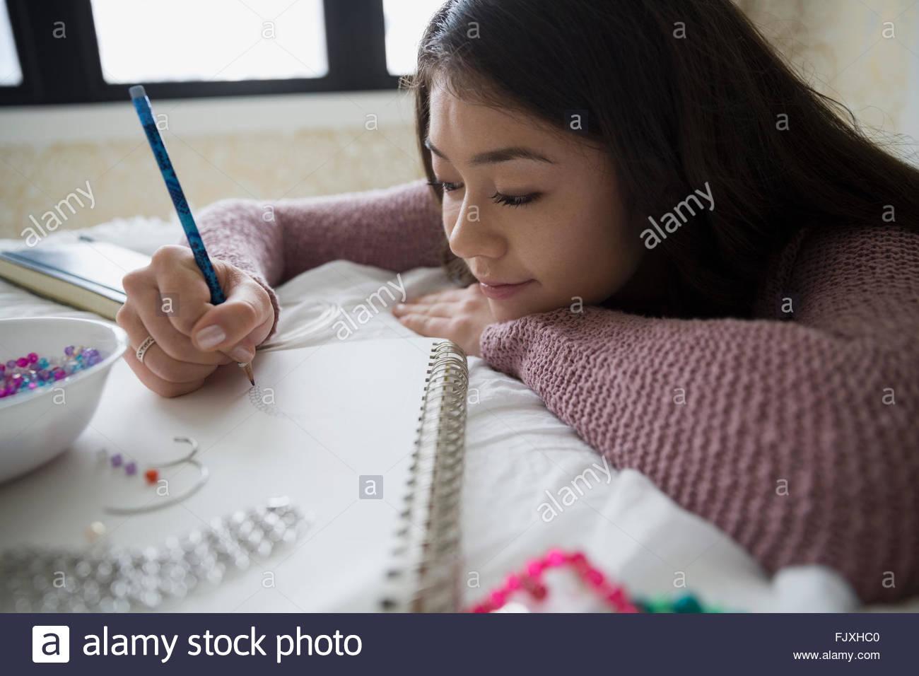 Adolescente à dessiner et à fabriquer des bijoux Photo Stock