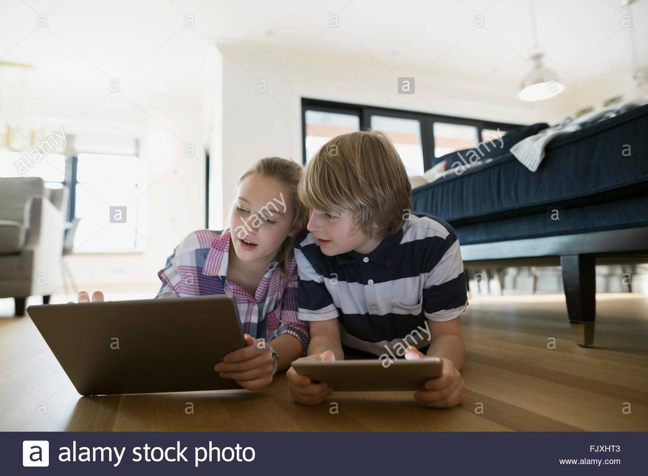 Frère sœur à l'aide de tablettes numériques plancher du salon Photo Stock