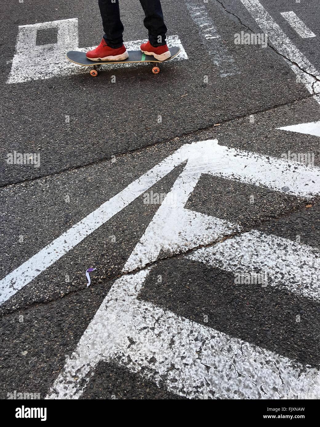 La section basse de l'homme sur la planche à roulettes Photo Stock