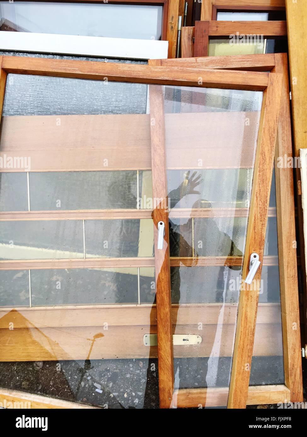 La réflexion de l'homme sur porte en verre à l'atelier Photo Stock