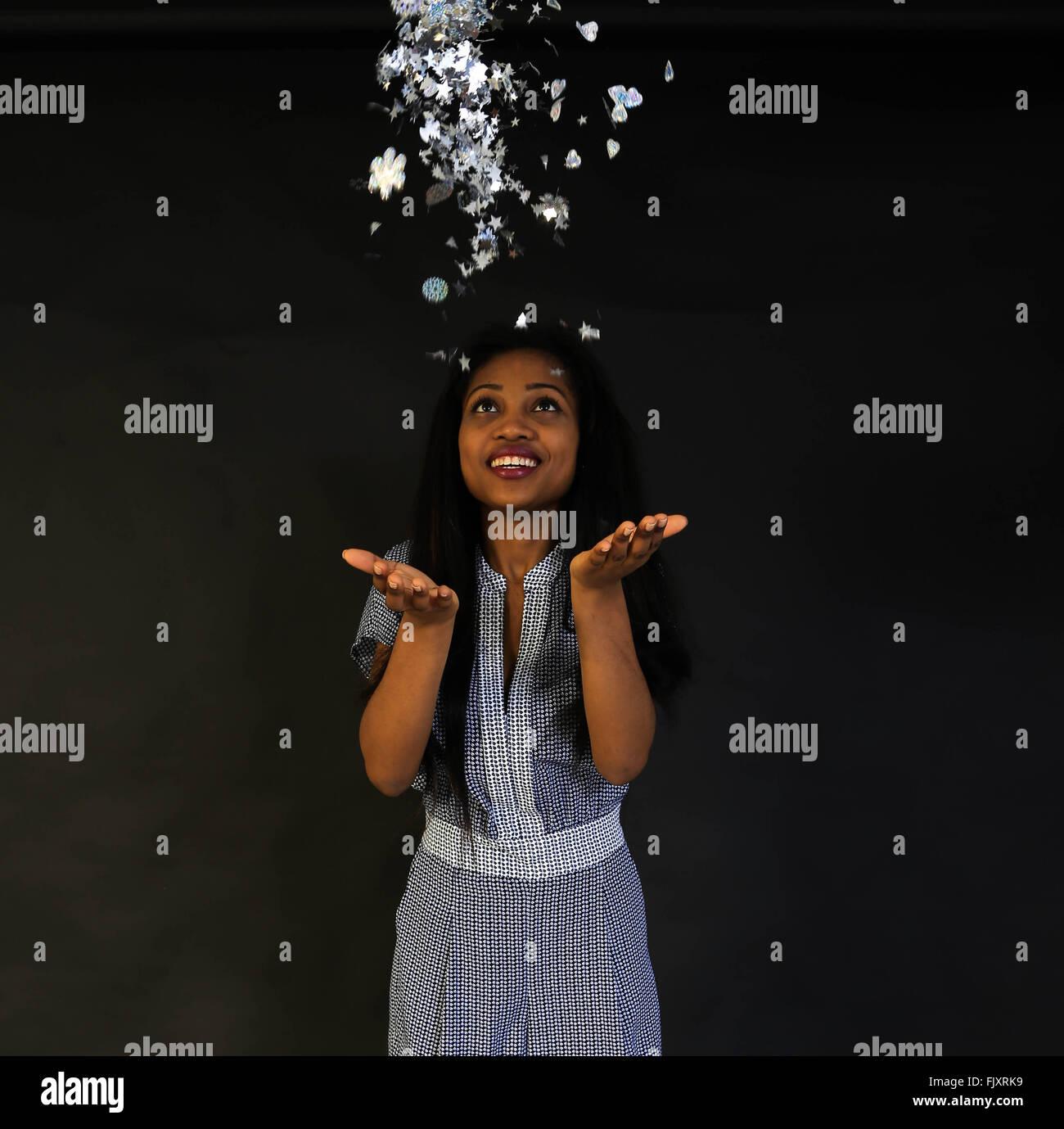 Cheerful Woman Throwing Objets de décoration contre l'arrière-plan de couleur Photo Stock