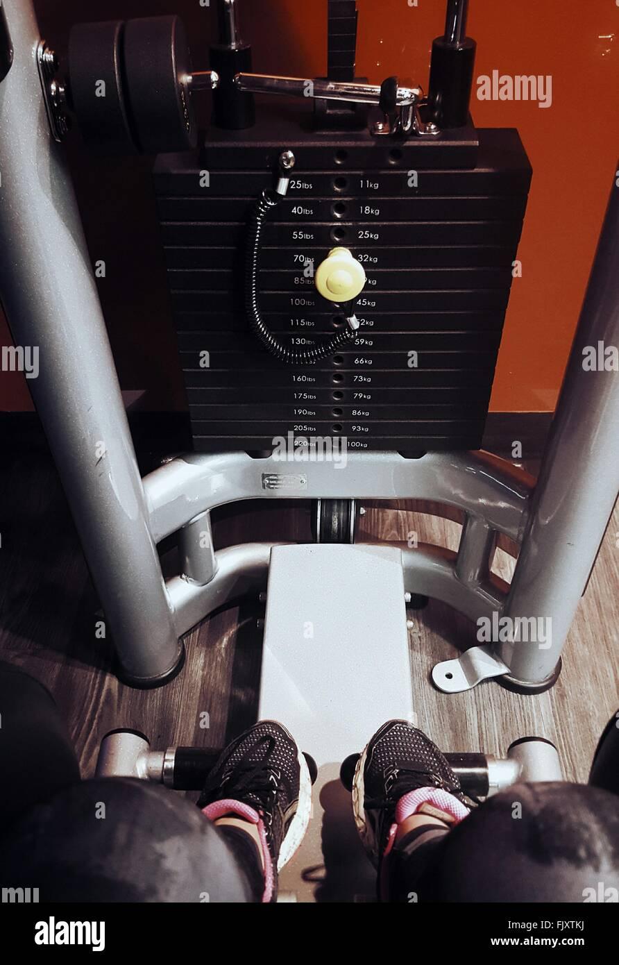 La section basse de femme par machine d'exercice à la salle de sport Photo Stock