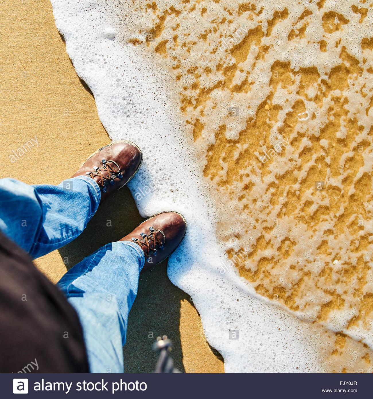 La section basse de l'Homme portant des chaussures sur le rivage à Beach Photo Stock