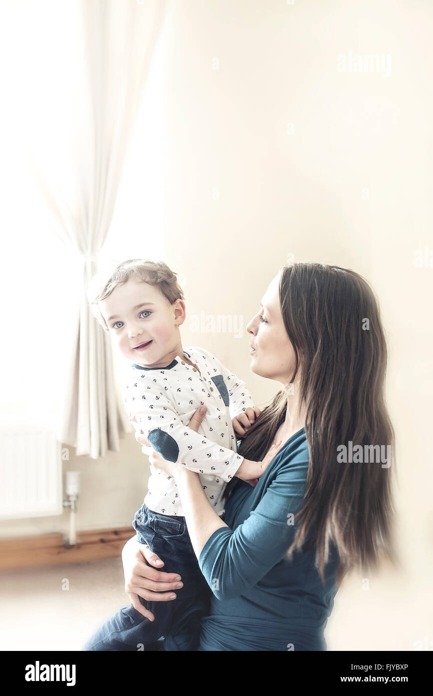 Jeune maman avec un petit garçon dans ses bras à la maison Photo Stock