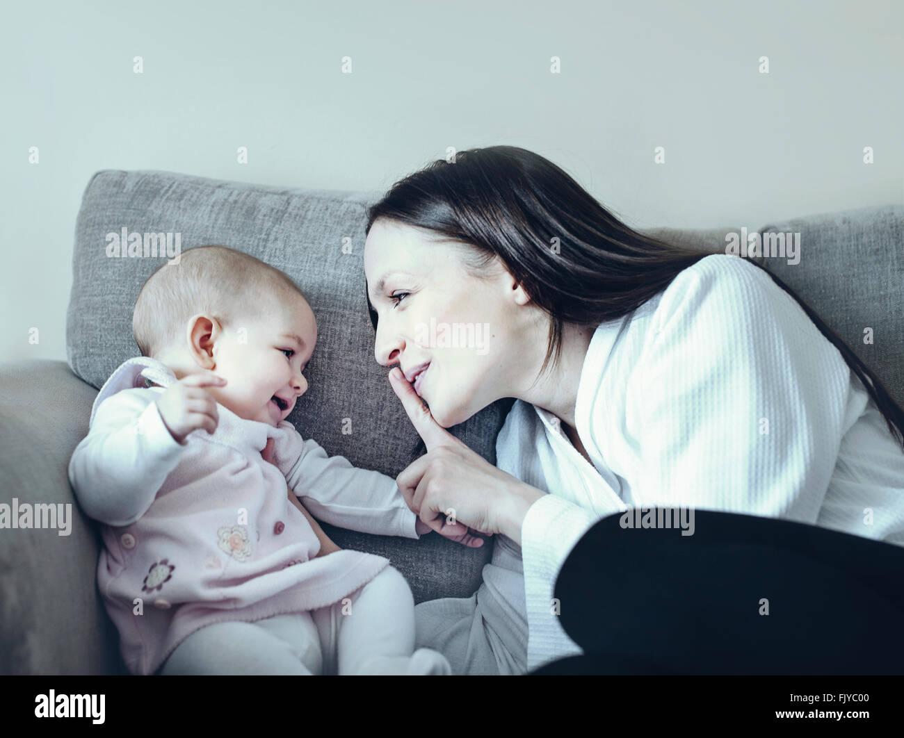 Jeune femme jouant avec son bébé sur le canapé-lit Photo Stock