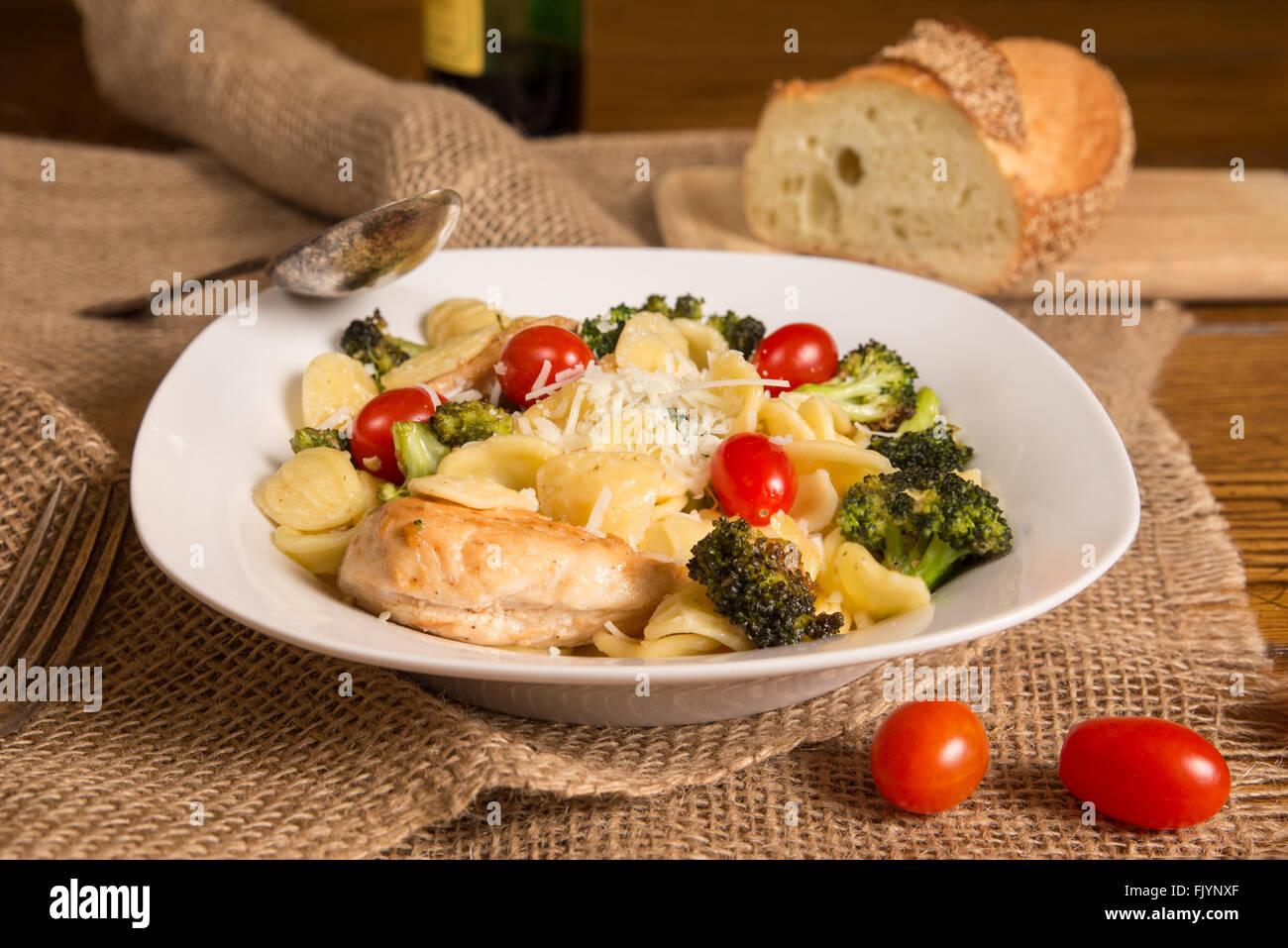Repas italien authentique avec des pâtes orecchiette, poulet, brocoli, tomates. Miche de pain italien et bouteille Photo Stock
