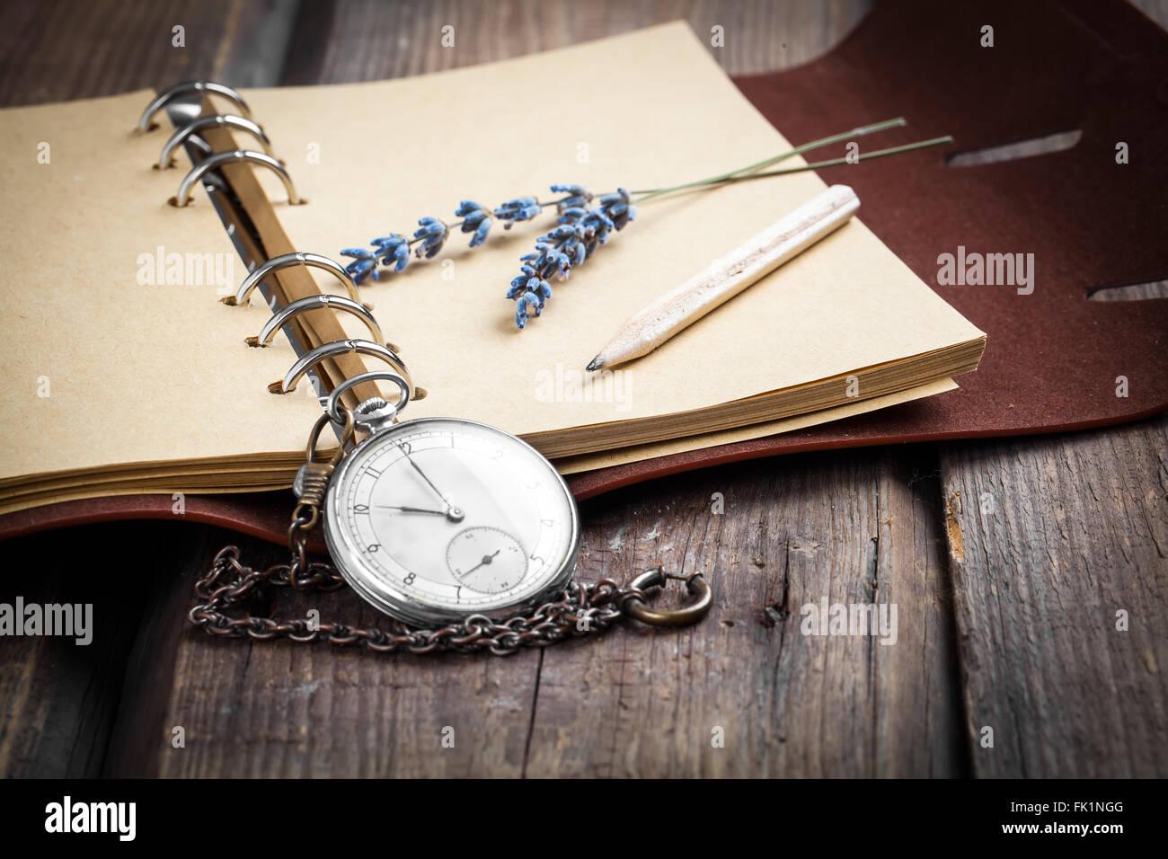 Grunge Vintage still life with pocket watch, fleurs de lavande et de vieux livre. Photo Stock