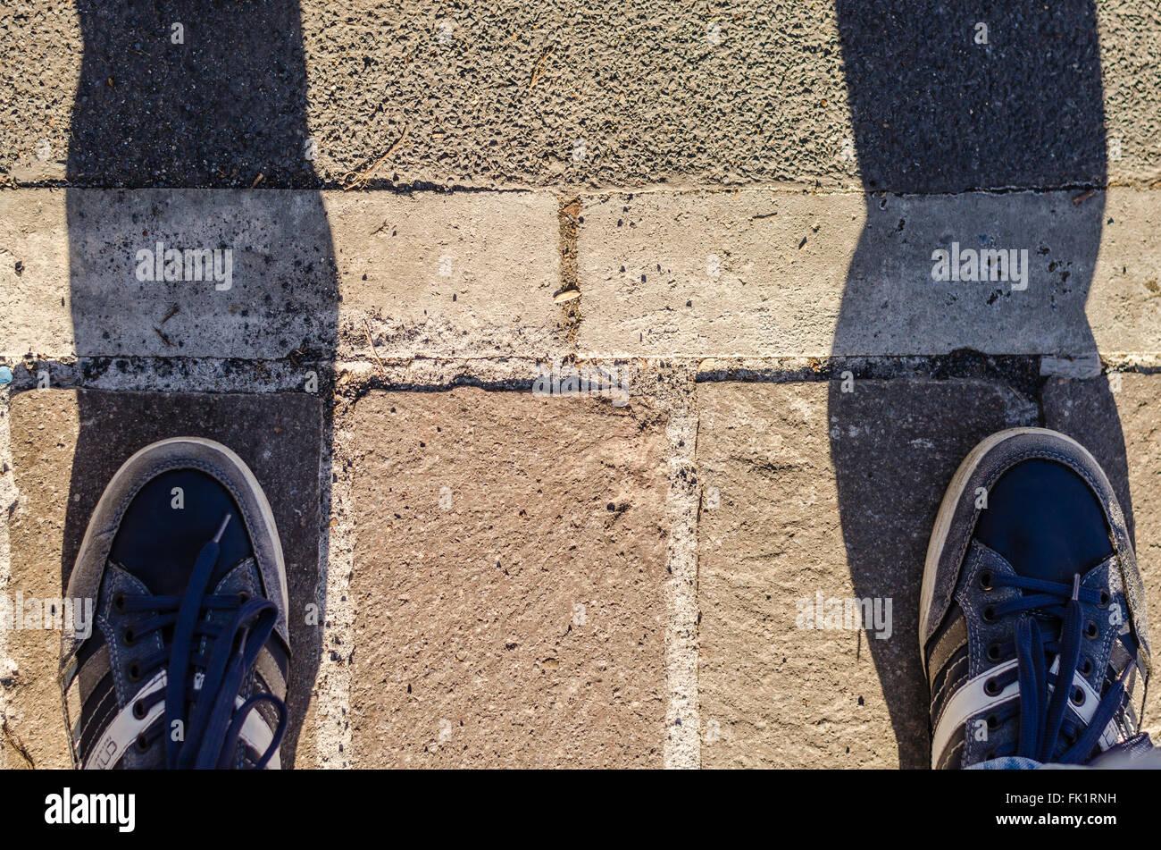 Je suis bloqué, deux pieds bloqués avant de franchir la ligne. symbole de la peur du changement et de Photo Stock