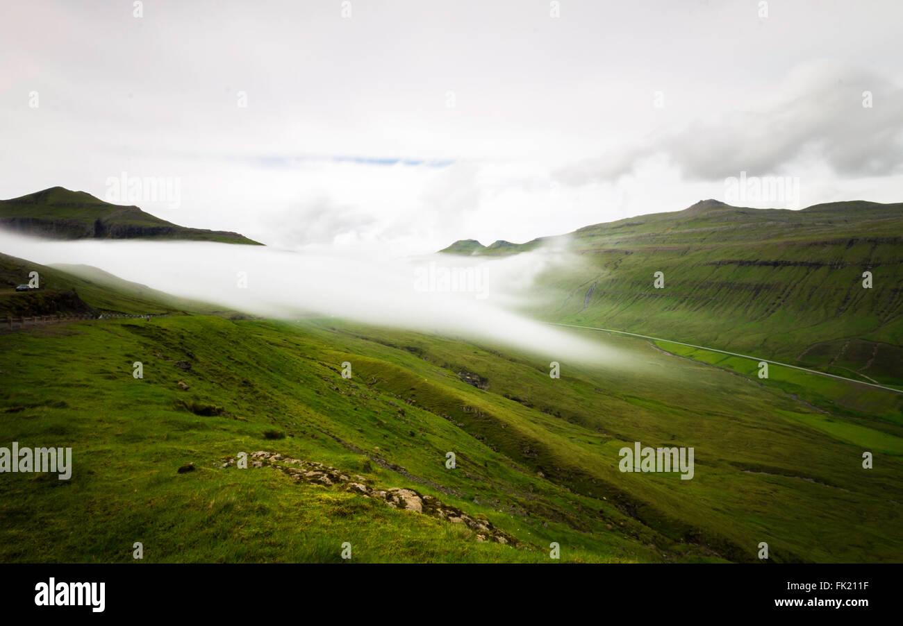Le brouillard se trouvant sur les montagnes. Îles Féroé, Danemark, Europe. L'exposition longue Photo Stock