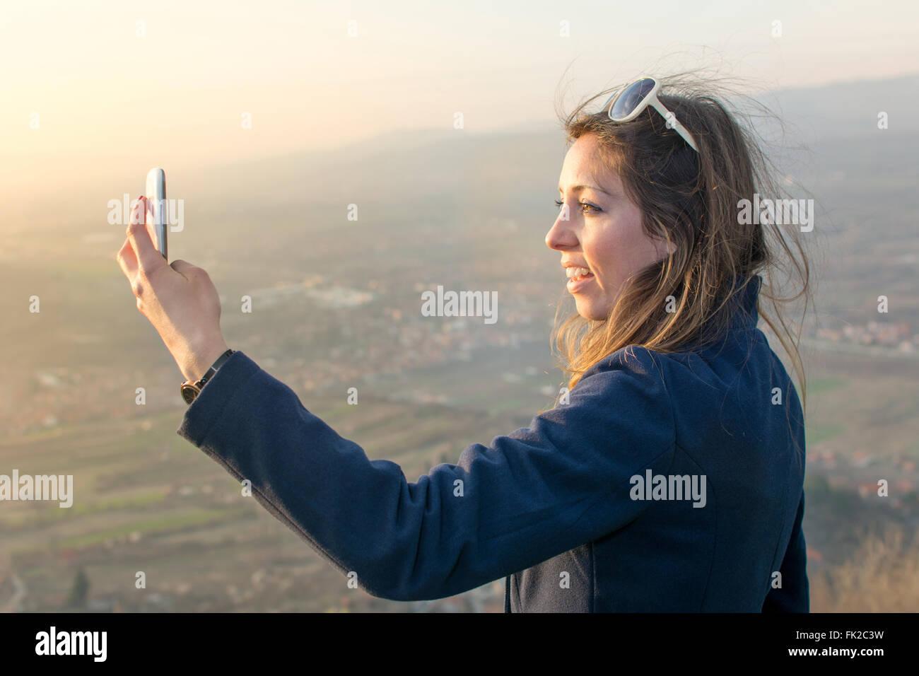 Prendre une fille en randonnée selfies au coucher du soleil Photo Stock