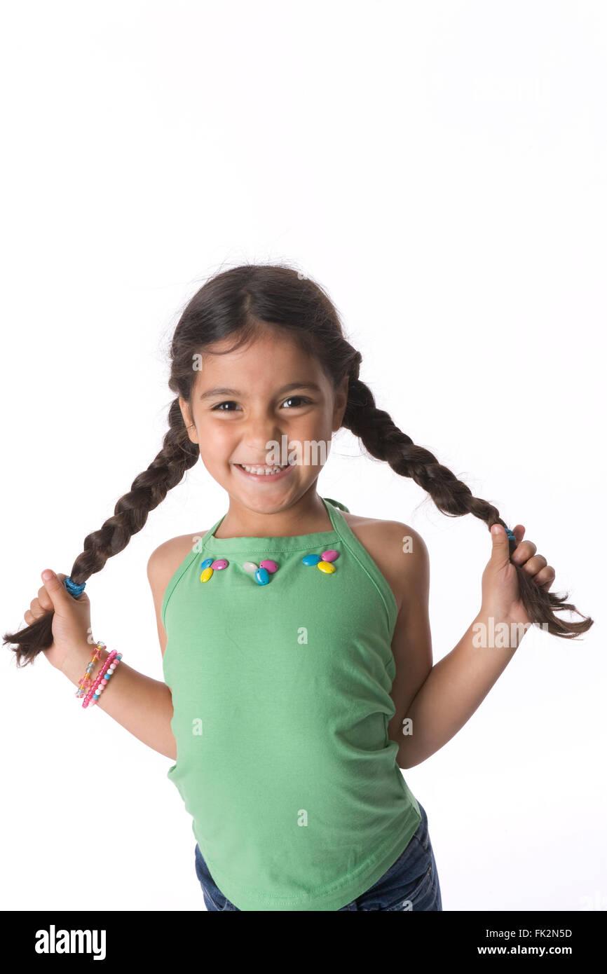 Petite fille est montrant ses tresses avec une expression timide sur fond blanc Photo Stock